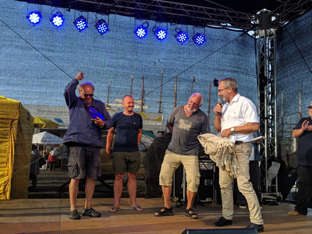 The lucky winners of the 2019 Hajkutter Regatta, the crew of the GROENNE ERNA, receive their prize from the mayor of Guldborgsund Municipality, John Brædder. Photo: Susanne Gidzinski/Hanse Sail